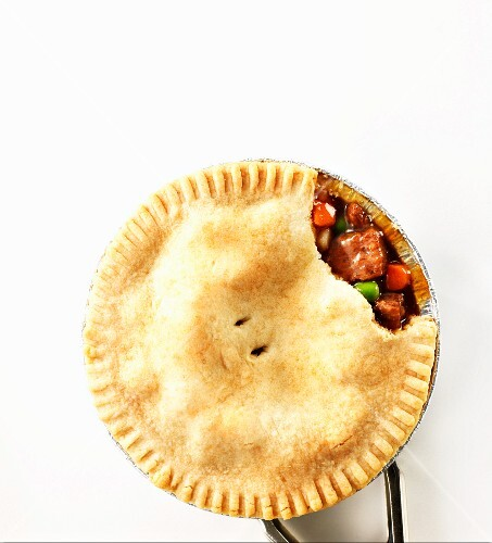 A beef pie with a piece removed