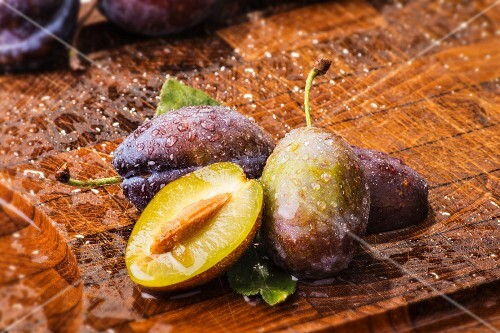 Freshly washed plums on a wooden board