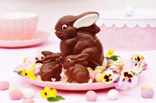 A family of chocolate Easter bunnies in a nest of flowers and sugared eggs