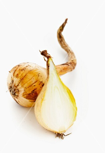 Pearl onions, whole and halved on a white surface (cut-out)