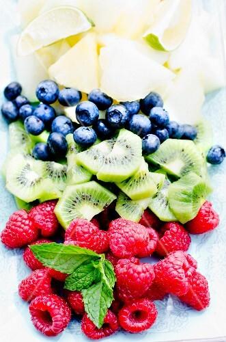Fresh fruit (blueberries, kiwis, raspberries) with mint leaves