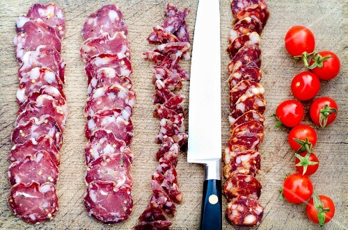 Slices of salami and chorizo on a chopping board with a knife and cherry tomatoes