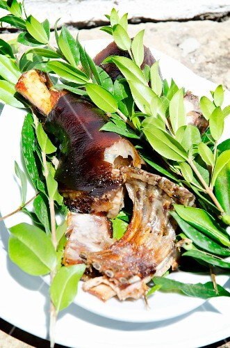 A piece of roast suckling pig on a plate with sprigs of fresh myrtle spurge (Sardinia)