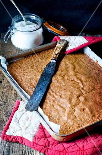 A sponge tray bake cake with a knife and sugar