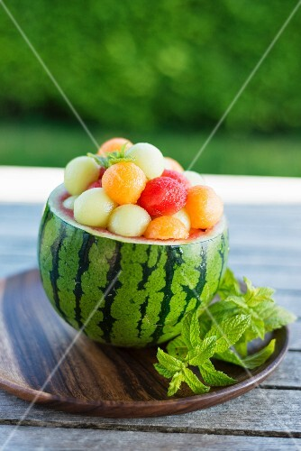 A hollowed out watermelon filled with various different melon balls
