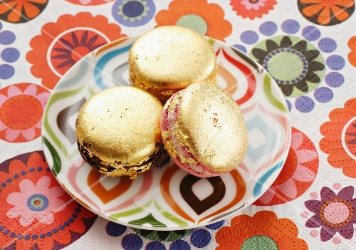 Golden macaroons on a colourful plate