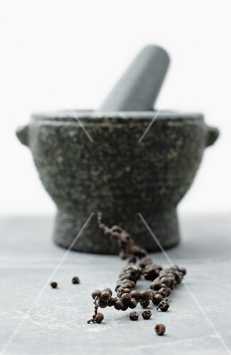 A vine of black peppercorns in front of a mortar