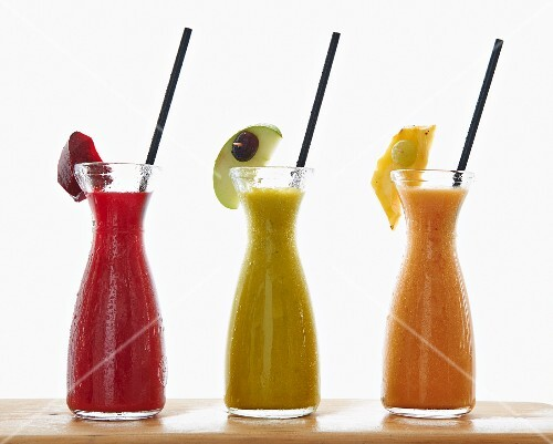 Three different smoothies in carafes