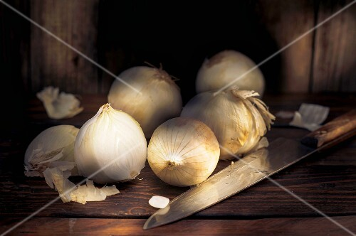 White onions on a wooden table with a knife