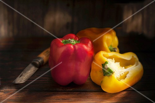 Red and yellow peppers, whole and halved