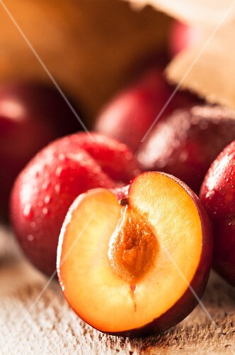 Red plums with drops of water, whole and halved