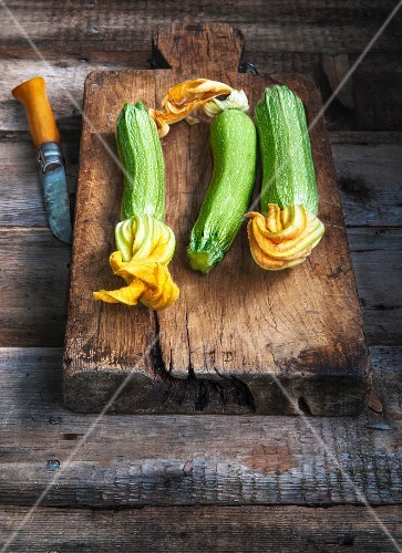 Courgettes with flowers on an old chopping board