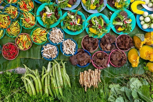 Mushrooms and various vegetables for sale at a market in Thailand