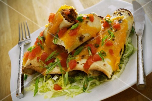 Beef enchiladas with spring onions and tomatoes