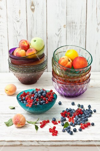 Blueberries, redcurrants, peaches, apples and lemons in glass bowls