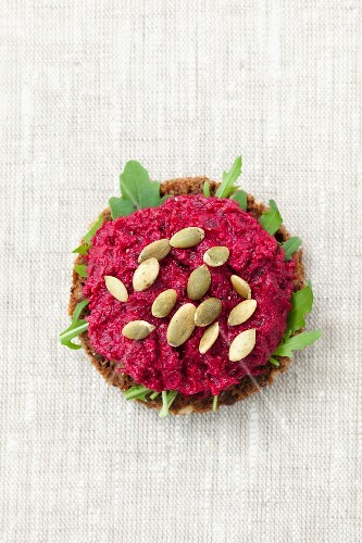 A slice of wholemeal bread topped with beetroot paste and pumpkin seeds