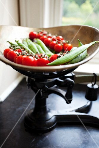 Cherry tomatoes and pea pods on an old pair of kitchen scales