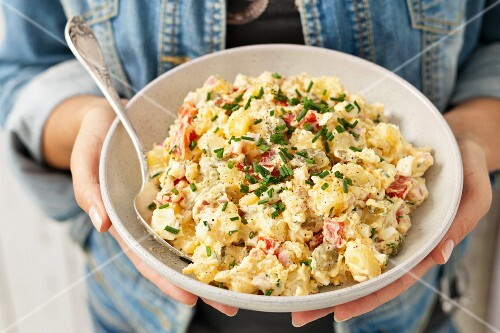 A woman holding a bowl of potato salad with gherkins, peppers, Gouda and mayonnaise