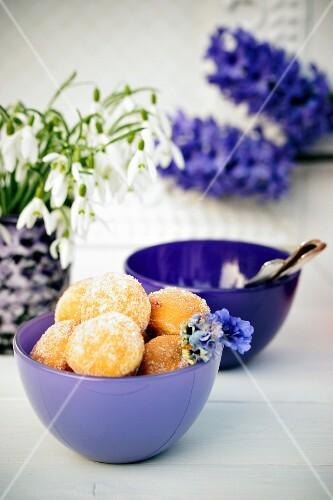 Mini-Krapfen in lila Schale, im Hintergrund Schneeglöckchen & Hyazinthen