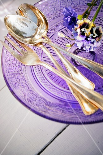 Purple flowers and silver cutlery on a glass purple plate