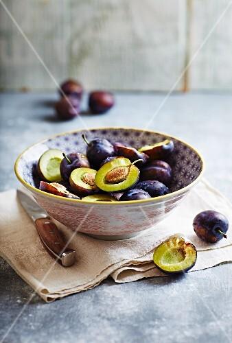Fresh plums in a ceramic bowl