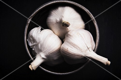 Three garlic bulbs in a bowl on a dark surface