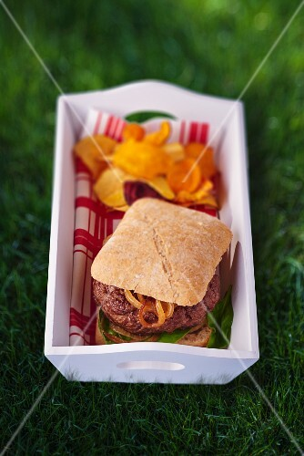 A hamburger with vegetable crisps for a picnic