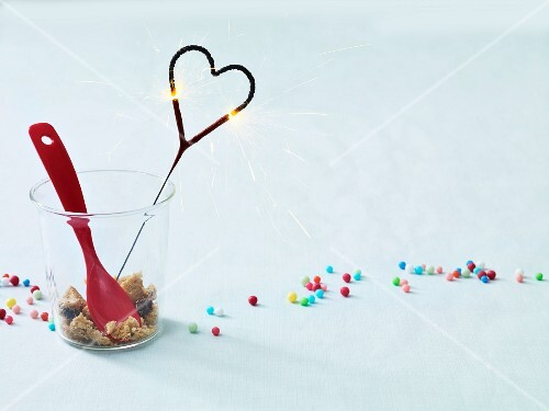 Colourful sugar sprinkles and a burning heart-shaped sparkler