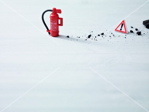 A visual metaphor for avoiding kitchen accidents making use of a mini fire extinguisher and a warning triangle