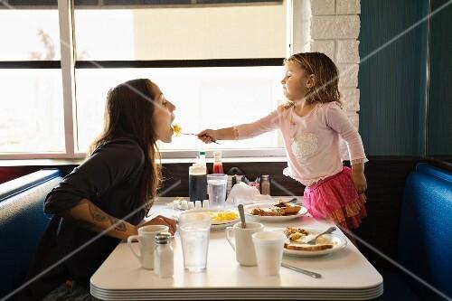 A little girl feeding her mother in a restaurant