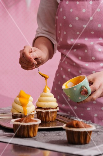Cupcakes being decorated with mango sauce