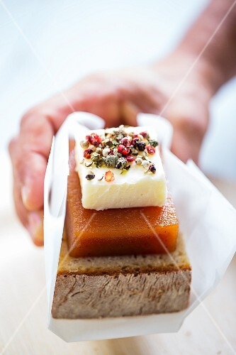 A hand holding cornbread with cheese and quince jelly