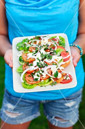 A woman holding a plate of Greek salad