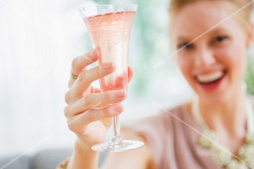 A young woman toasting with a glass of champagne