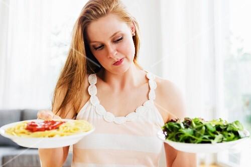 A woman choosing between pasta and salad