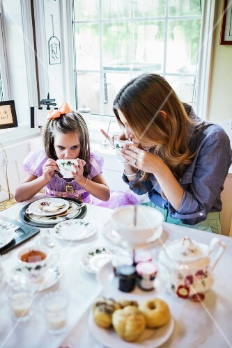 A mother and daughter having tea in a dining room