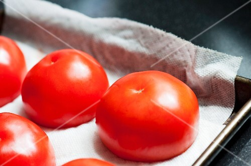 Hollowed out tomatoes on a baking tray