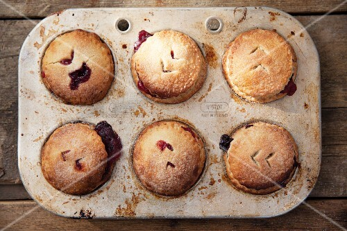 Apple and blackberry pies in a baking tin