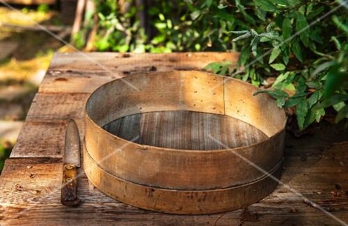 An old flour sieve on a wooden table in a garden