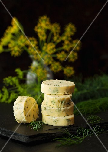 Slices of dill butter stacked in front of dill flowers