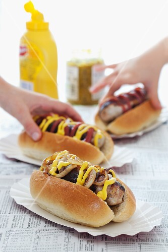 Children's hands taking hot dogs with mustard and ketchup