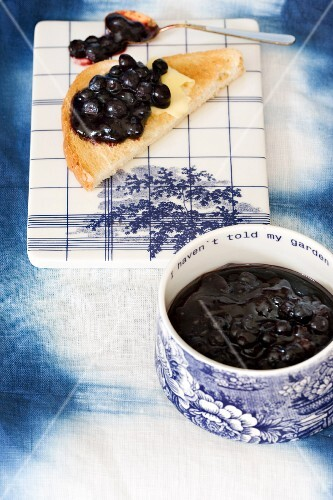 Blueberry jam in a pot and on a slice of toast