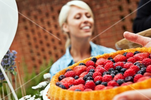 Two friends with a fruit flan at a garden party