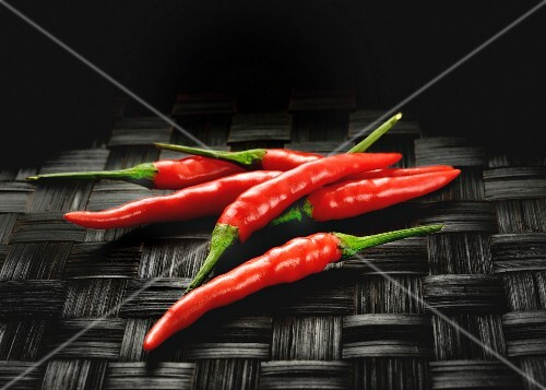Red chilli peppers on a black woven mat