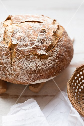 A rustic loaf of bread next to a bread basket