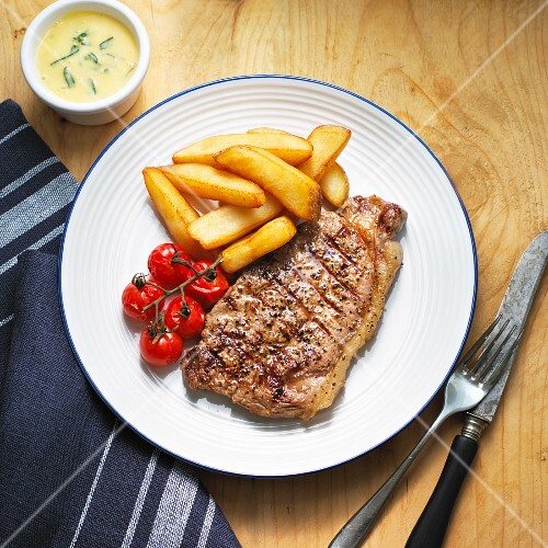 Beef steak with Bearnaise sauce, chips and cherry tomatoes
