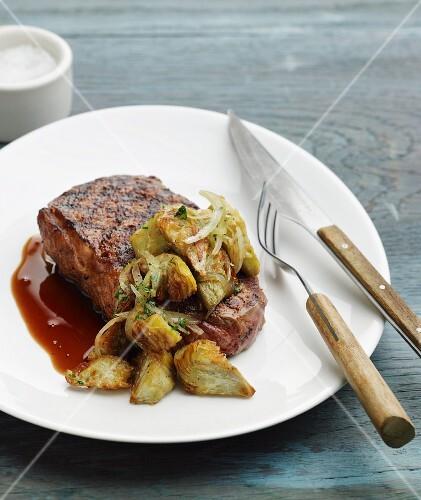 New York strip steak with artichokes and dark gravy