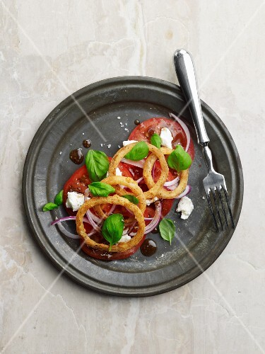 Fried onion rings with goat's cheese and tomatoes
