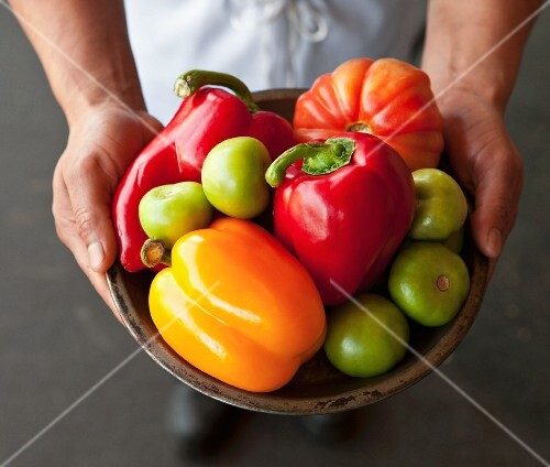 A chef holding a bowl of peppers, tomatillos and tomatoes