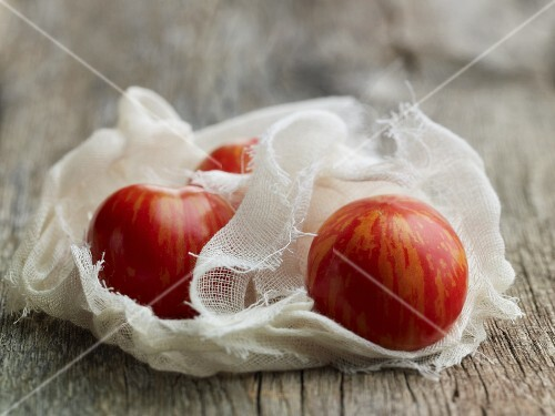 Stripped organic tomatoes in a muslin cloth
